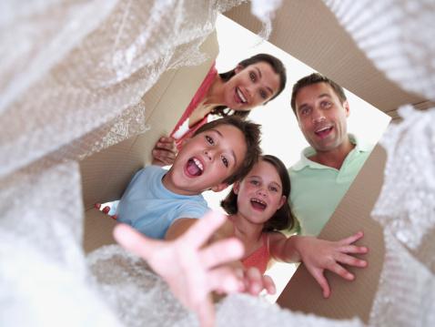 Deux parents et leur deux enfants qui déballent un carton de déménagement