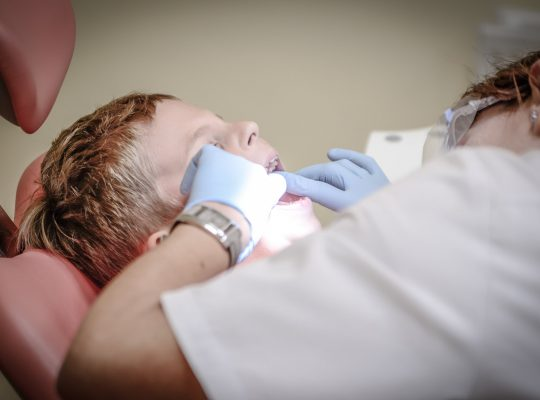 Dentiste qui examine les dents d'un enfant