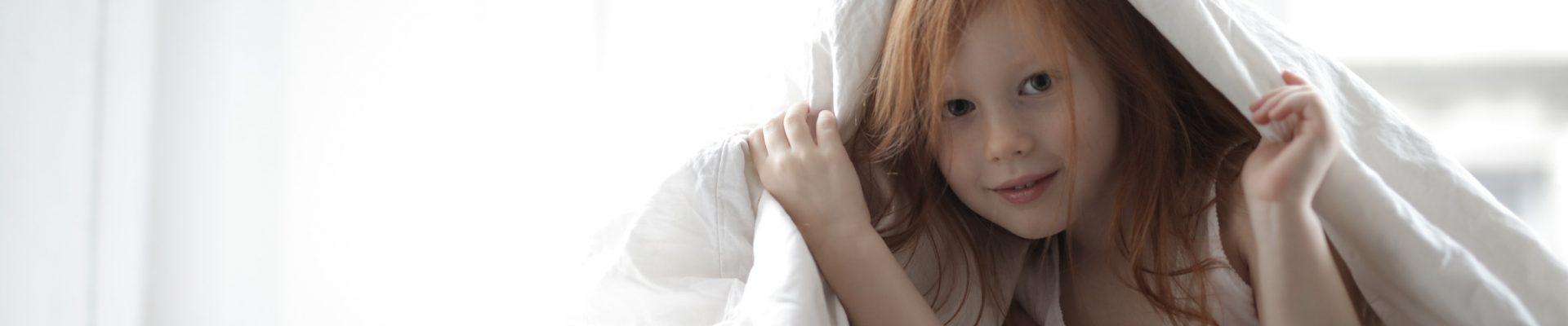 Petite fille qui se cache sous sa couette de lit