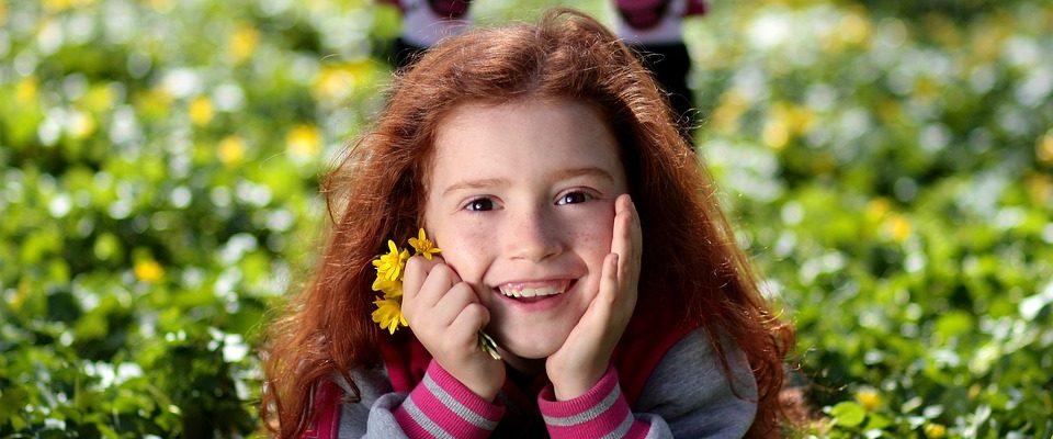 Petite fille rousse souriante dans l'herbe