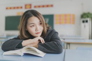 Jeune femme appuyée contre un livre ouvert avec un air pensif