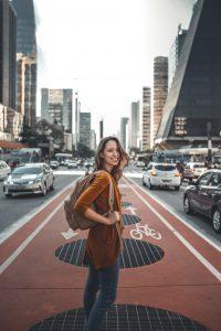 Jeune femme en voyage avec un sac à dos dans une grande ville