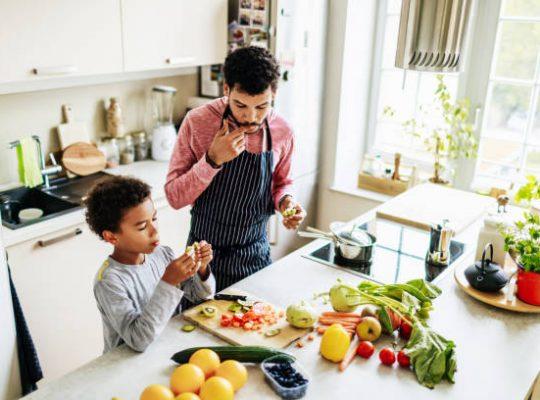 Père qui cuisine une salade de fruits avec son fils