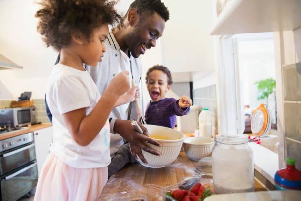 Père qui apprend à ses enfants à cuisiner