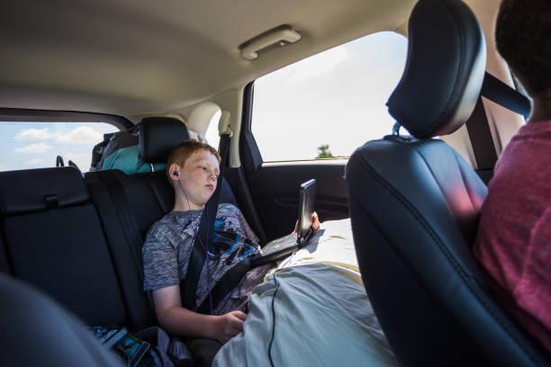 Petit garçon qui regarde un film sur un lecteur DVD dans la voiture