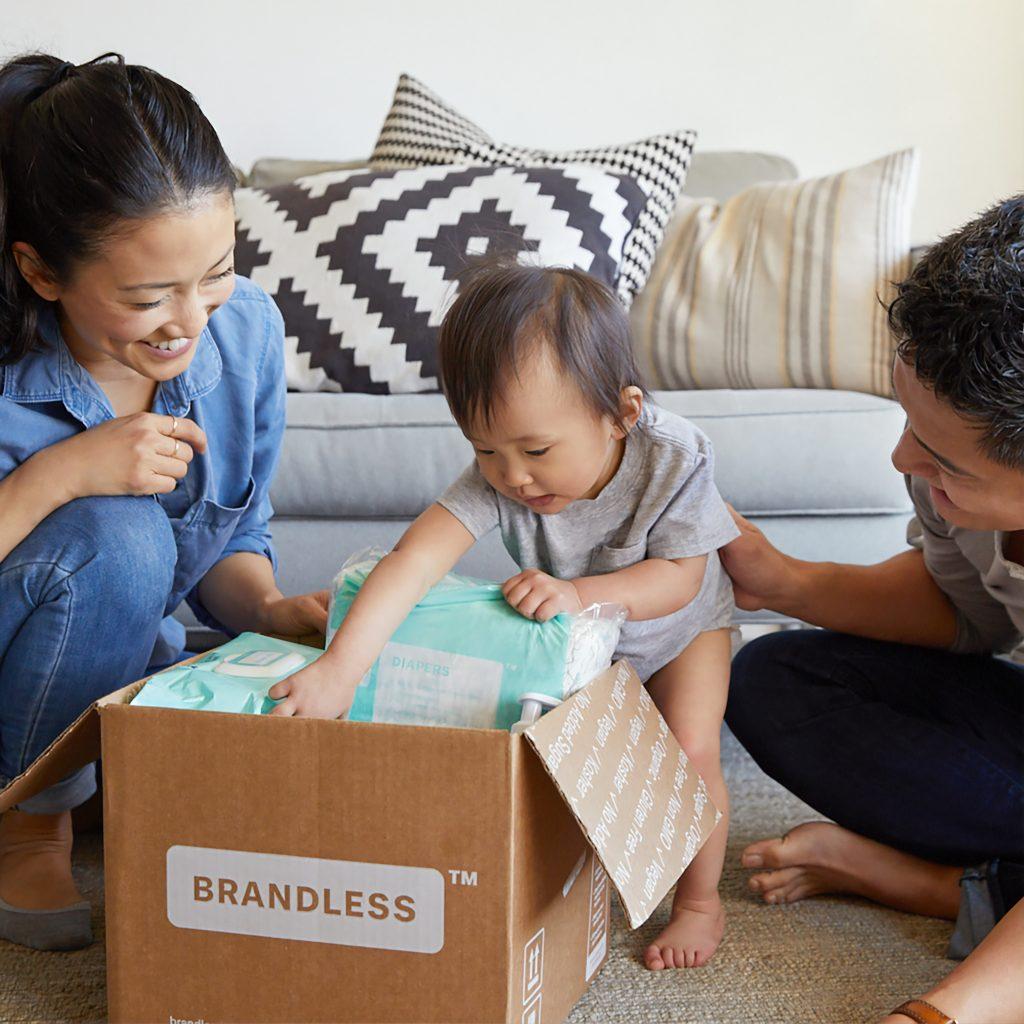 deux parents qui entourent leur bébé qui regarde le contenu d'un carton