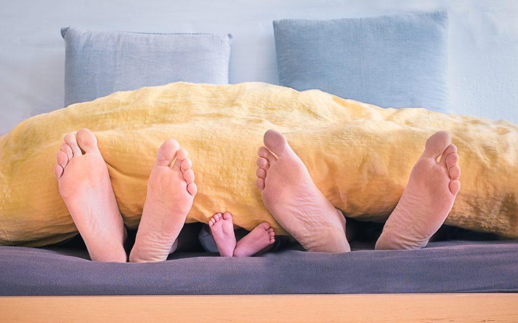 Couple au lit avec leur enfant en pyjamas