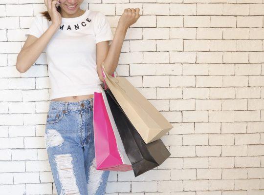 femme portant un jean déchiré et un t-shirt blanc tenant des sacs de shopping devant un mur en briques blanches
