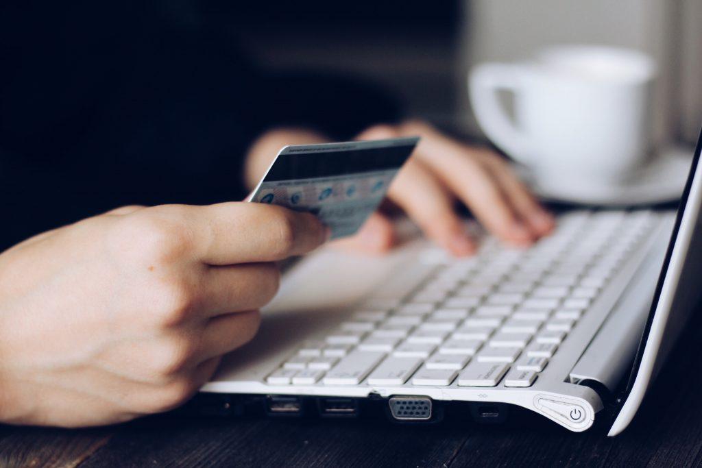 zoom sur les mains d'une personne tenant une carte de crédit près d'un clavier d'ordinateur et faisant du shopping en ligne